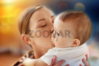 close up of happy young mother kissing little baby