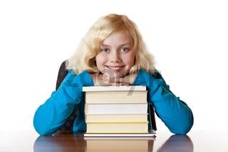 Schulmädchen lehnt am Schreibtisch glücklich auf Schulbüchern