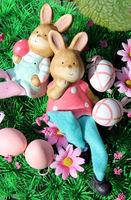 Zwei Osterhasen liegen auf einer Blumenwiese mit bunten Eiern