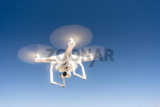 White Quadcopter Drone Flying Hoovering Blue Sky