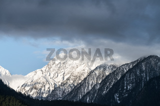 snow capped mountain and misty clouds