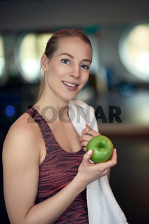 Attractive young woman athlete holding an apple