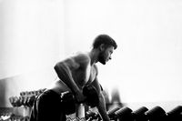 Monochrome shot of a ripped shirtless man exercising with dumbbe
