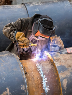 Worker with protective mask welding metal with sparks and smoke