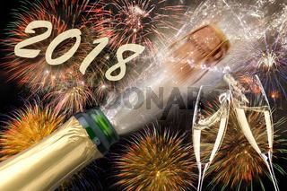 Knallender Korken auf Champagnerflasche mit Feuerwerk zu Neujahr 2018
