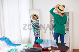 woman packing travel bag at home or hotel room