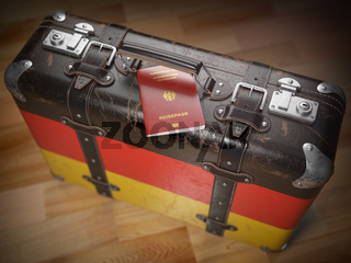 Travel or immigration concept. Passport of Germany and suitcase with flag of Germany