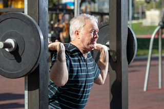 Elderly man lifting weights in Outdoors Gym