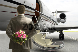 Mann mit Blumenstrauß am Flugzeug