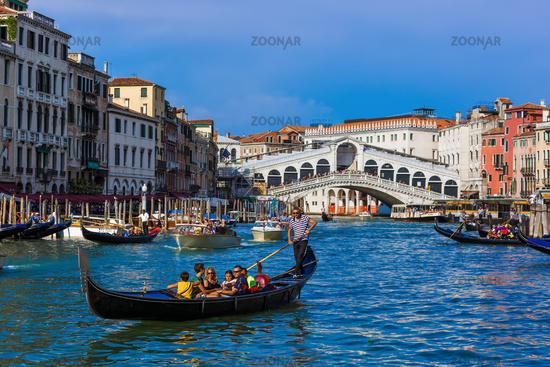 VENICE, ITALY - AUGUST 21, 2016: Tourists ride in gondola near Rialto bridge on August 21, 2016 in Venice Italy
