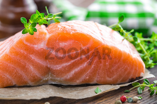 Raw salmon fish fillet on wooden board closeup