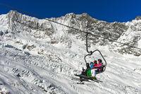 Skifahrer auf einem Sessellift vor dem Feegletscher und dem Dom Gipfel,Skigebiet Saas-Fee,Schweiz