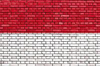 flag of Monaco painted on brick wall