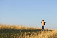 Hiker blue sky with binoculars meadow