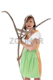 Junge hübsche bayrische Frau im Dirndl attackiert mit Heugabel.Freigestellt auf weissem Hintergrund