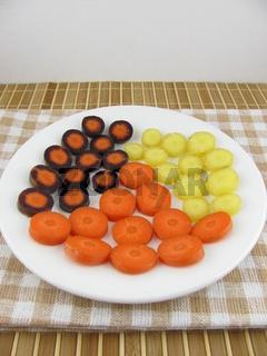 Geschnittene frische bunte Möhrenstücke auf einem Teller