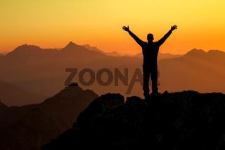 Happy success winning man on summit arms up at sunset