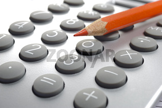 red pencil laying on top of calculator