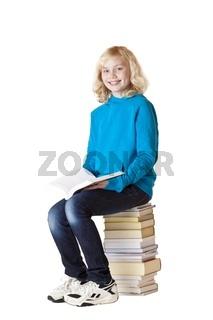 Glückliches Schulmädchen liest ein Buch und sitzt auf Schulbüche