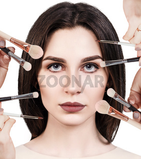 Many hands doing make up to glamour woman.