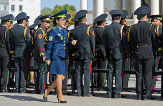 Frau in Uniform passiert männliche Mitglieder der mongolischen Streitkräfte bei einer Parade
