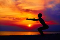 Silhouette of woman standing at yoga pose on the beach during an amazing sunset