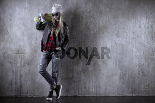 Blond teenager girl in black sunglasses and pink hat with blue skateboard. In front of concrete wall.