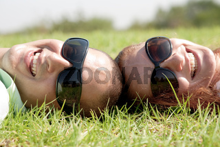 A young couple laying down and  smiling on a grass lawn