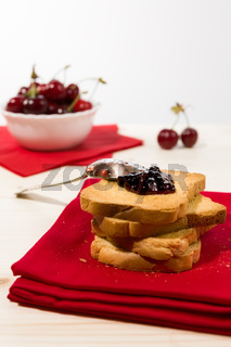 Rusk with cherry jam over a red napkin