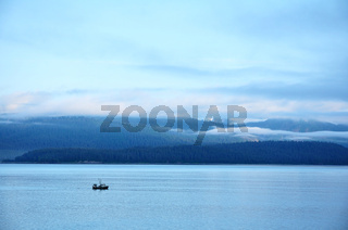 Fishing Boat with Mountains and Low Clouds