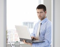 Young businessman standing with laptop in hand