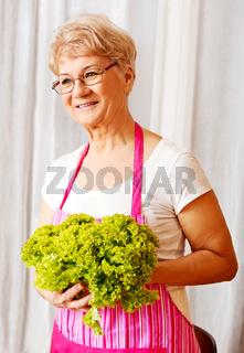Senior woman holding green salad