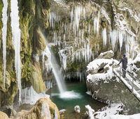 Traveler man enjoying icicles and waterfall on cold winter hike. Hinanger Waterfall, Bavaria, Germany