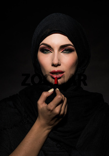 Muslim woman putting lipstick