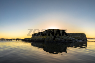 Fredriksholm, remains of an old fortress on an islet in Kristiansand, blue and golden sky and sea.