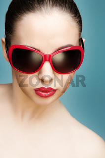 close up studio portrait of young beautiful woman wearing red sunglasses