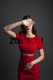 Pretty young sexy model female with dark hair in amazing red dress