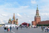 People walk near a temporary stage built on the Red Square