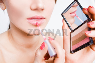 girl doing her make-up using lipgloss and mirror