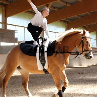 Mädchen voltigiert auf Pferd