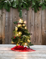Small Christmas tree decoration on rustic wood with snowy background