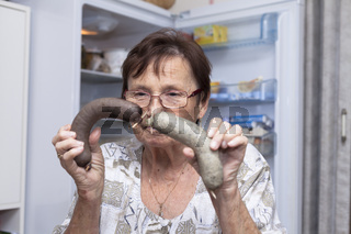 Senior woman holding pork liver sausages