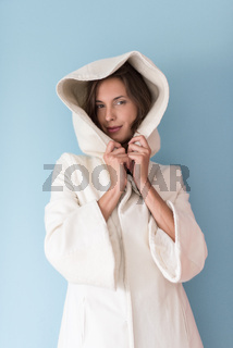 woman in a white coat with hood isolated on blue background