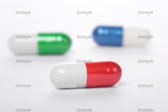 Closeup of three capsule on white background.