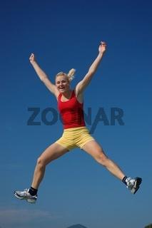 Blonde junge Frau macht einen Freudensprung in die Luft