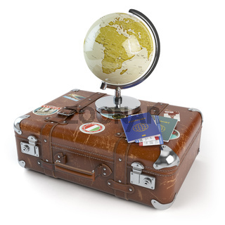 Travel or tourism concept. Old suitcase with stickers, globe and passports with boarding pass tickets isolated on white background.