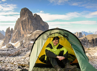 Man sitting relaxed in tent and smiling happy. Great mountains.