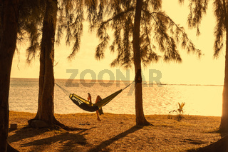 Woman reading tablet in hammock