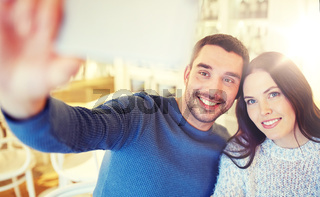 couple taking smartphone selfie at cafe restaurant