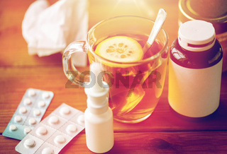cup of tea, drugs, honey and paper tissue on wood